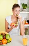 Junge Schönheitsfrau, die Fruchtsalat isst Stockfoto