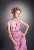Junge Schönheitsfrau, die im rosafarbenen Kittel aufwirft Lizenzfreie Stockbilder