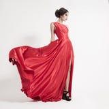 Junge Schönheitsfrau in flatterndem rotem Kleid. Weißer Hintergrund. Lizenzfreies Stockbild