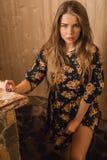 Junge Schönheitsfrau gegen Hausinnenraum Stockfoto