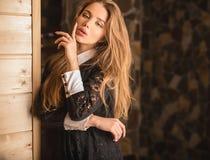 Junge Schönheitsfrau gegen Hausinnenraum Stockfotos