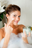 Junge Schönheitsfrau im Bad unter Verwendung der Gesichtsmaske Stockfotos