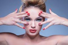 Junge Schönheitsfrau mit den Händen, die ihr Gesicht und Augen gestalten lizenzfreie stockfotos