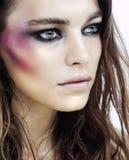 Junge Schönheitsfrau mit Make-up mögen Glanzschuß auf Gesicht Stockbild