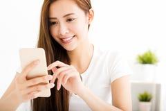 Junge Schönheitslesemitteilung mit intelligentem Telefon Stockfotografie