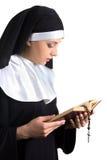 Junge Schönheitsnonne mit der Bibel und Rosenbeet lokalisiert auf Whit Stockbild