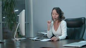 Junge sch?ne asiatische Gesch?ftsfrau mit Kopfh?rer im B?ro stock video footage