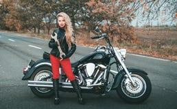 Junge sch?ne kaukasische Frau, die mit Motorrad aufwirft lizenzfreies stockfoto