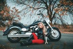 Junge sch?ne kaukasische Frau, die mit Motorrad aufwirft stockfotos