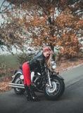 Junge sch?ne kaukasische Frau, die mit Motorrad aufwirft stockbilder