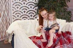 Junge sch?ne Mutter mit ihrer kleinen Tochter, die ein Buch sitzt auf der Couch liest stockfoto