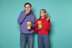 Junge sch?ne Paare in der zuf?lligen Kleidung, die das Popcorn, gebohrt w?hrend eines langweiligen Films isst stockbilder