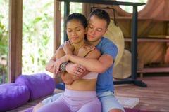 Junge sch?ne und exotische asiatische Balinesefrau, die thail?ndische Massage der K?rperheilung durch attraktiven kaukasischen Ma stockfotografie