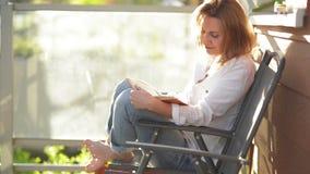 Junge Sch?nheit, die interessantes Buch auf Terrasse, w?hrend Sunny Days liest stock video