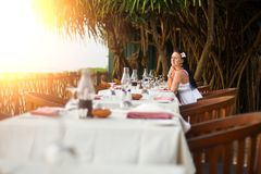 Junge Sch?nheit im wei?en Kleid auf dem Ufer des tropischen Meeres in einem Caf? Reise- und Sommerkonzept lizenzfreie stockbilder