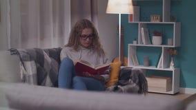 Junge Sch?nheit liest ein Papierbuch in ihrem gem?tlichen Wohnzimmer am Abend stock video