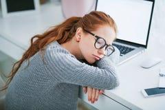Junge Sch?nheit mit dem roten Haar, die tragenden Gl?ser, arbeitend im B?ro, benutzt einen Laptop und einen Handy lizenzfreie stockbilder