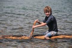 Junge schaufelt ein Floß auf See stockfotos
