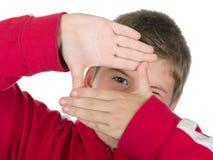 Junge schaut durch einen Rahmen von den Händen Stockfotos