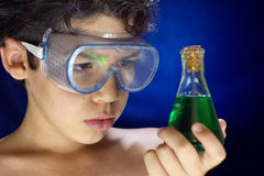 Junge schaut wissenschaftliches Experiment stockbild