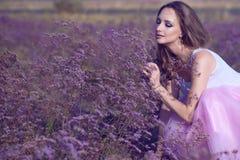 Junge schicke Frau mit künstlerischem bilden und riechende violette Blumen des langen Fliegenhaares mit geschlossenen Augen Stockfotografie