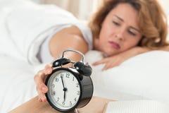 Junge schläfrige Frau, die versucht, den Wecker abzustellen Stockfotos