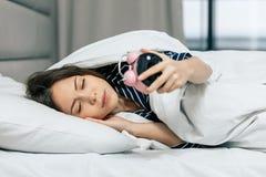 Junge schlafende Frau, die Wecker im Schlafzimmer betrachtet lizenzfreie stockfotos