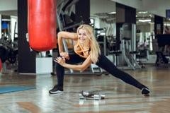 Junge schlanke blonde Frau, die Übungen in der Turnhalle tut Lizenzfreies Stockfoto