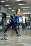 Junge schlanke blonde Frau, die Übungen in der Turnhalle tut Stockfoto