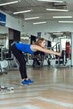 Junge schlanke blonde Frau, die Übungen in der Turnhalle tut Stockfotografie