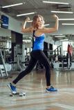 Junge schlanke blonde Frau, die Übungen in der Turnhalle tut Stockfotos