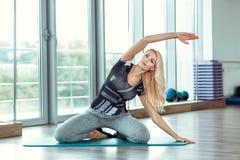 Junge schlanke blonde Frau, die Übungen in der Turnhalle tut Lizenzfreie Stockfotos
