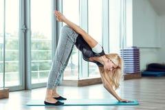 Junge schlanke blonde Frau, die Übungen in der Turnhalle tut Lizenzfreies Stockbild