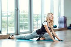 Junge schlanke blonde Frau, die Übungen in der Turnhalle tut Lizenzfreie Stockbilder
