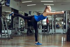 Junge schlanke blonde Frau, die Übungen in der Turnhalle tut Stockbild