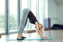 Junge schlanke blonde Frau, die Übungen in der Turnhalle tut Stockbilder