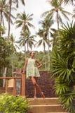 Junge schlanke Frau in einem tropischen Garten auf einem Hintergrund von Palmen und Anlagen Lizenzfreies Stockfoto