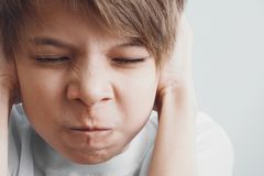 Junge schließt seine Ohren mit seinen Händen und Stirnrunzeln mit seinem mustert geschlossenes stockbild
