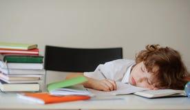 Junge schlief beim Sitzen an einem Schreibtisch ein Stockfoto