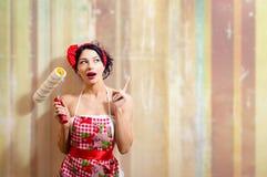 Junge schöne überraschte Frau, die Farbenrolle hält Stockbilder