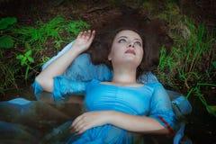 Junge schöne ertrunkene Frau, die im Wasser liegt Lizenzfreie Stockfotografie