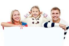 Junge schöne Familie hinter weißem unbelegtem Anzeigenvorstand Lizenzfreie Stockfotos