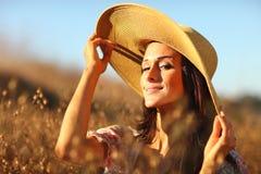 Junge schöne Frau auf einem Feld in der Sommerzeit Stockbilder
