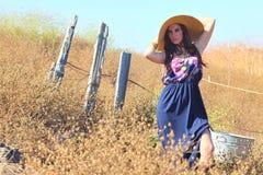 Junge schöne Frau auf einem Feld in der Sommerzeit Lizenzfreie Stockfotografie