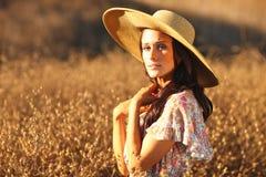 Junge schöne Frau auf einem Feld in der Sommerzeit Stockbild