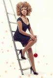 Junge schöne Frau, die eine Weihnachtskugel anhält Stockfotografie