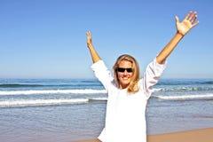 Junge schöne Frau, die am Strand glücklich ist Lizenzfreies Stockfoto
