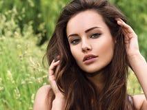 Junge schöne Frau mit den langen Haaren draußen Stockbild