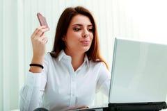 Junge schöne Geschäftsfrau, die Schokolade an ihrem Arbeitsplatz isst Lizenzfreie Stockfotos