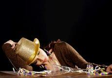 Junge schöne getrunkene Frau, die auf einer Tabelle schläft. Stockfotografie